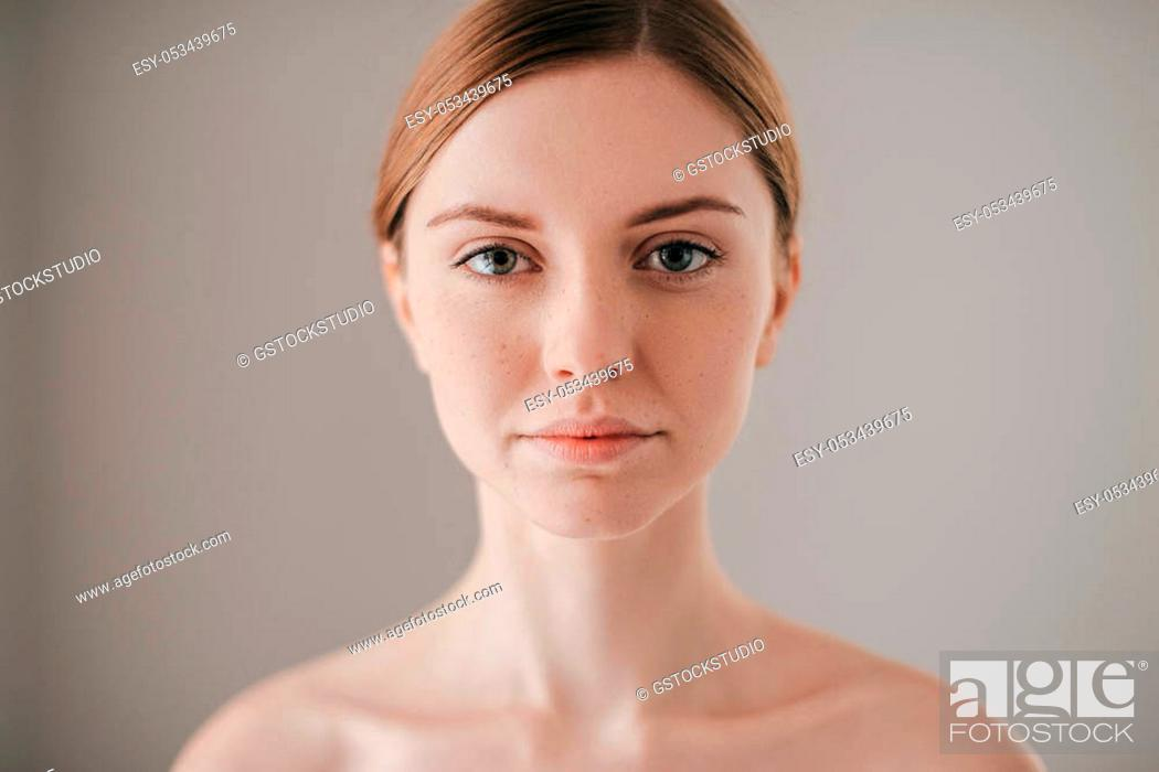 Stock Photo: Natural beauty. Portrait of redhead woman with freckles looking at camera while standing against grey background.