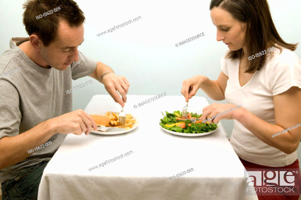 Stock Photo: Couple eating contrasting meals.