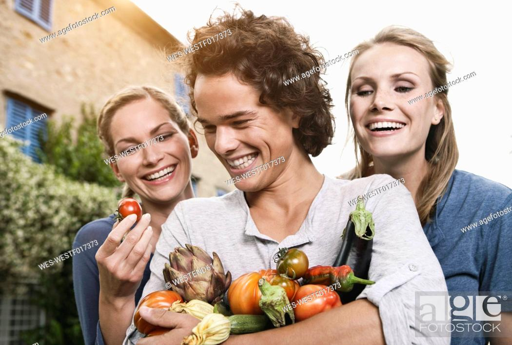 Stock Photo: Italy, Tuscany, Magliano, Young man and women holding vegetables, smiling.