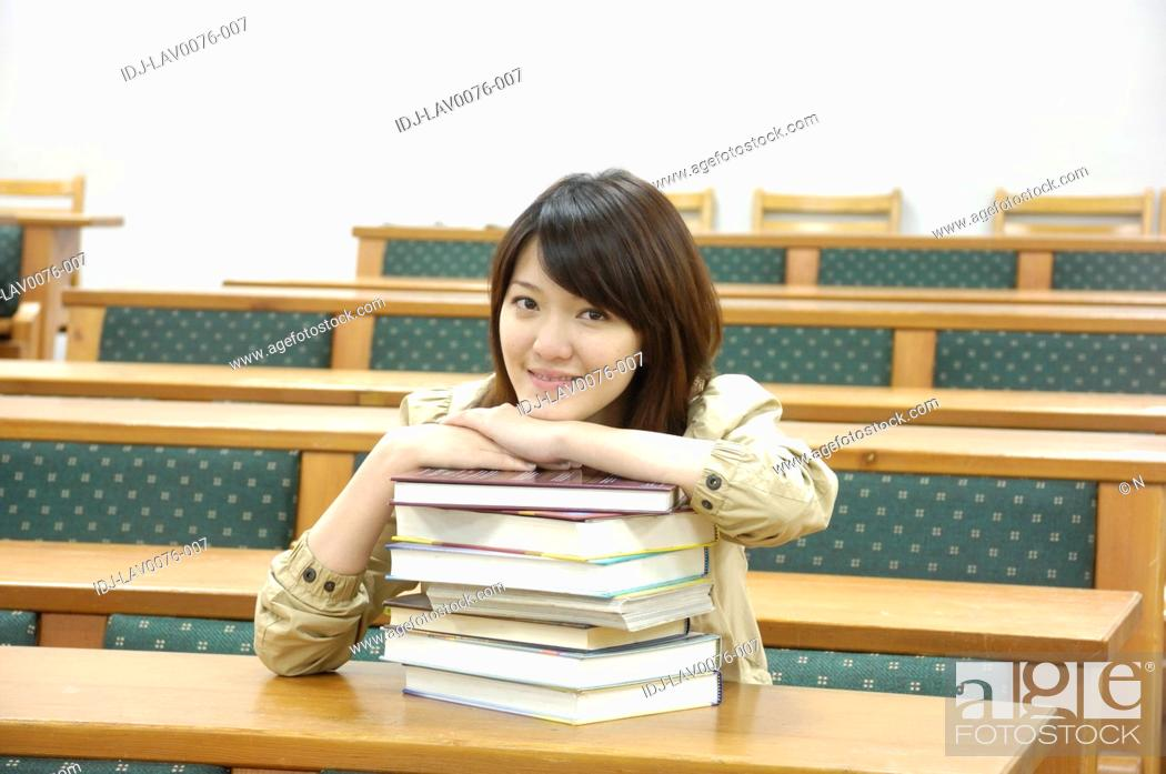 Stock Photo: Female university student leaning on a stack of books in a classroom.