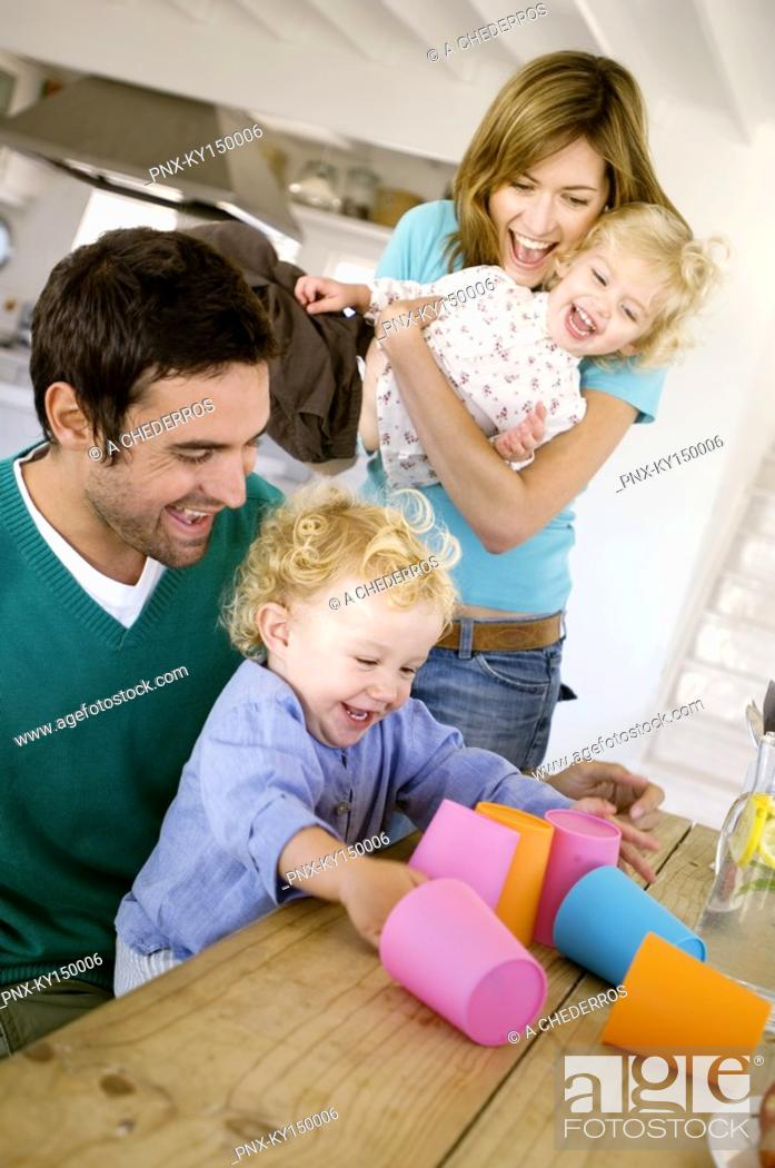 Stock Photo: Couple and 2 children playing in kitchen.