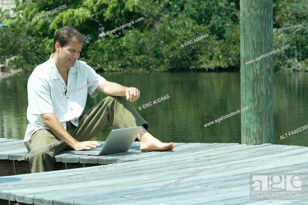 Stock Photo: Man sitting on dock, using laptop computer.
