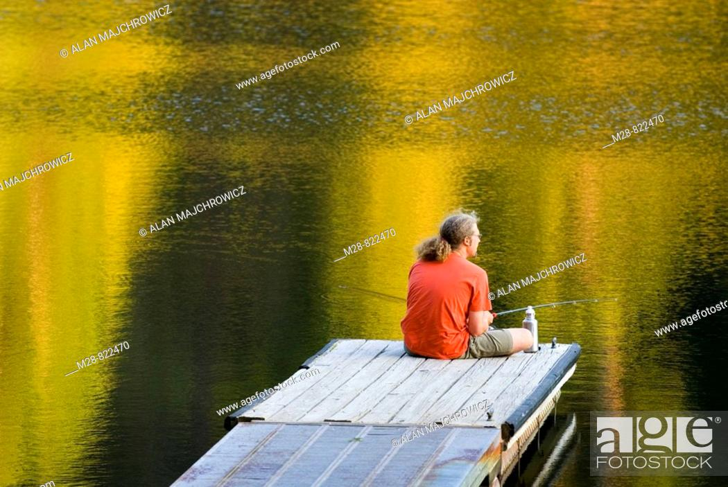 Stock Photo: Fisherman in red shirt trying his luck from a dock on Black Pine Lake North Cascades Washington USA.