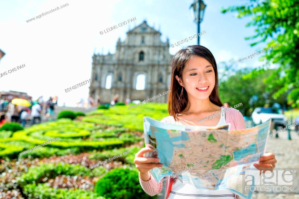 Stock Photo: Woman looking at city map with the background of Saint Paul's Cathedral in Macau.