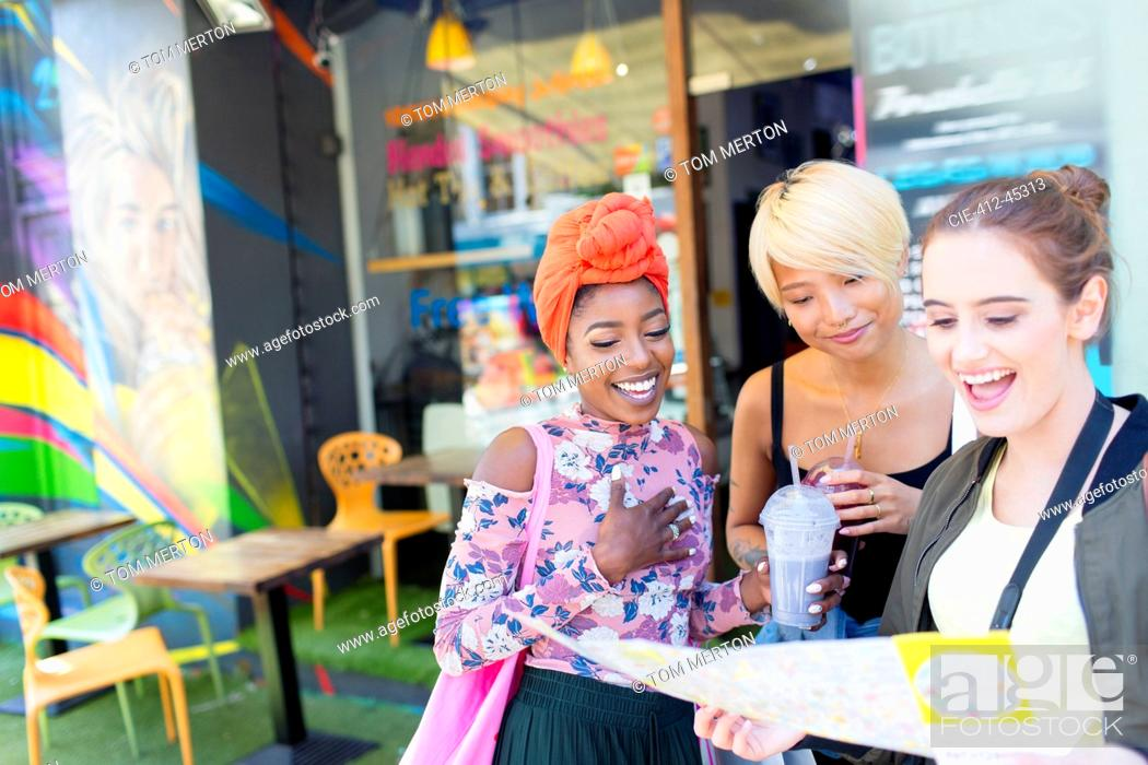 Stock Photo: Young women friends with map outside smoothie shop.