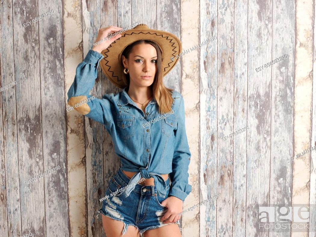 Stock Photo: young pretty woman in cowboy costume as well as cowboy hat.