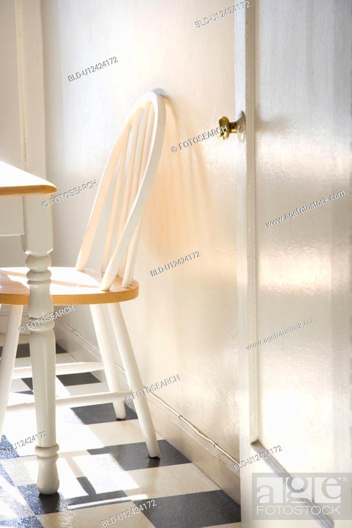 Stock Photo: Sunlight lit kitchen with dinette and black and white checkerboard tiled floor.