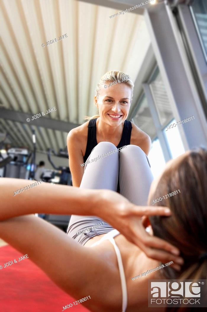 Stock Photo: Woman holding legs of woman doing sit ups in health club.