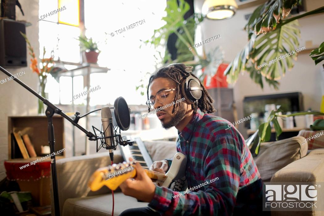 Stock Photo: Young male musician recording music, playing guitar at microphone in apartment.