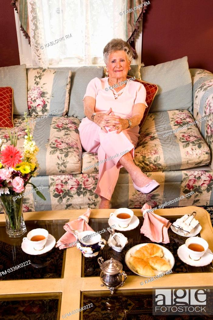 Stock Photo: Portrait of senior woman sitting on floral sofa in living room.