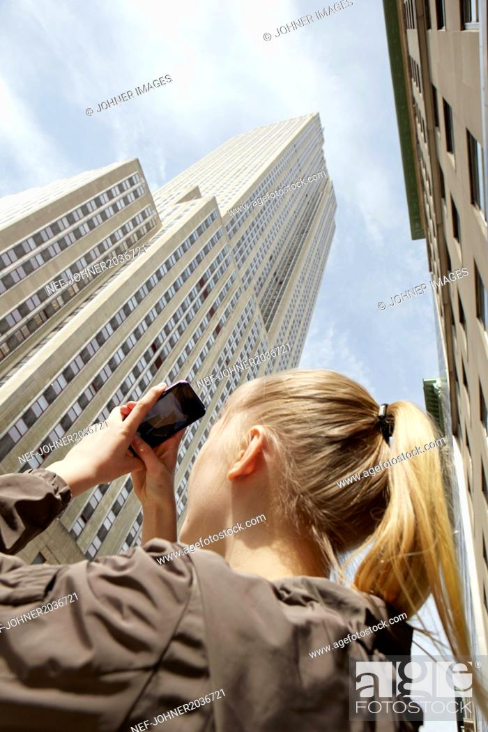 Stock Photo: Young woman taking photo of skyscraper with her smartphone.