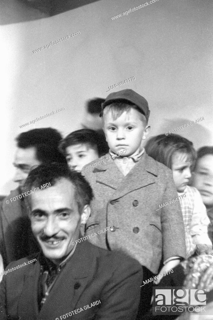 Stock Photo: UMBRIA padre e figlio, il primo sorridente e il secondo imbronciato, assistono ad uno spettacolo di stornellatori in un'osteria.