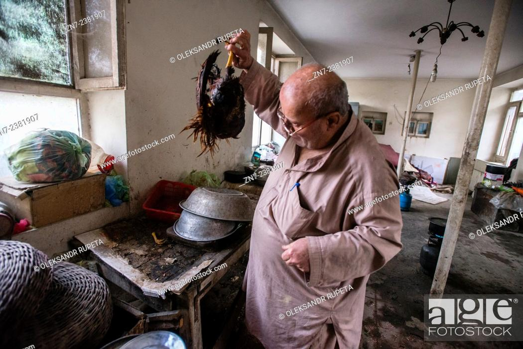 Stock Photo: Zabolon Simantov, the last Afghan Jew, prepares cock for the dinner in his kitchen, Kabul, Afghanistan.