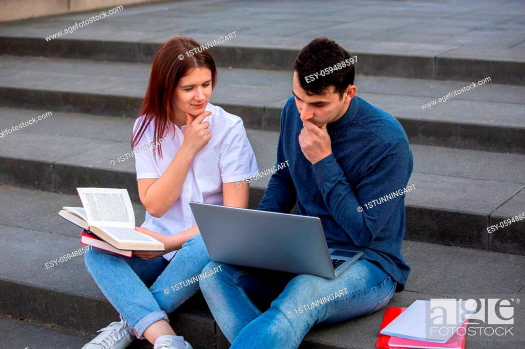 Stock Photo: Concentrated Students using laptop and books learning for the exam together on campus stairs. Students looking for an answer on the internet preparing exam.
