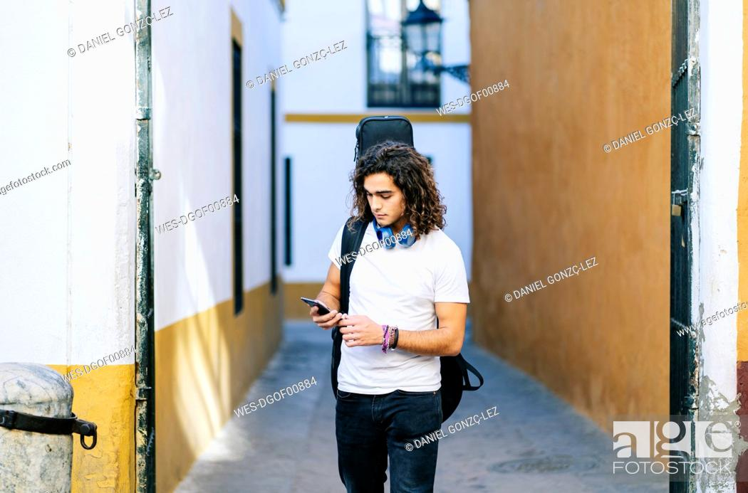 Imagen: Young man using mobile phone while walking on narrow street at Santa Cruz, Seville, Spain.