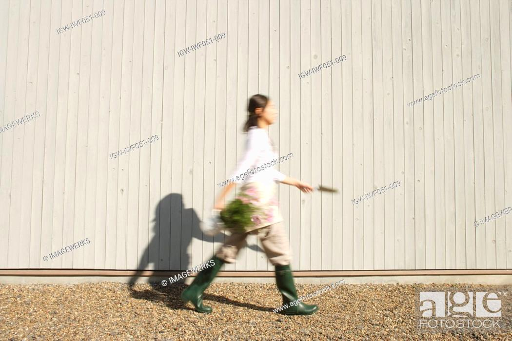 Stock Photo: Teenage girl 14-15 walking with shovel and potted plant.