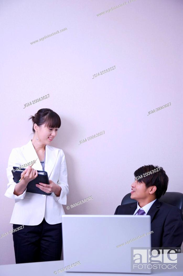 Stock Photo: Young man and woman talking in office and smiling at each other.
