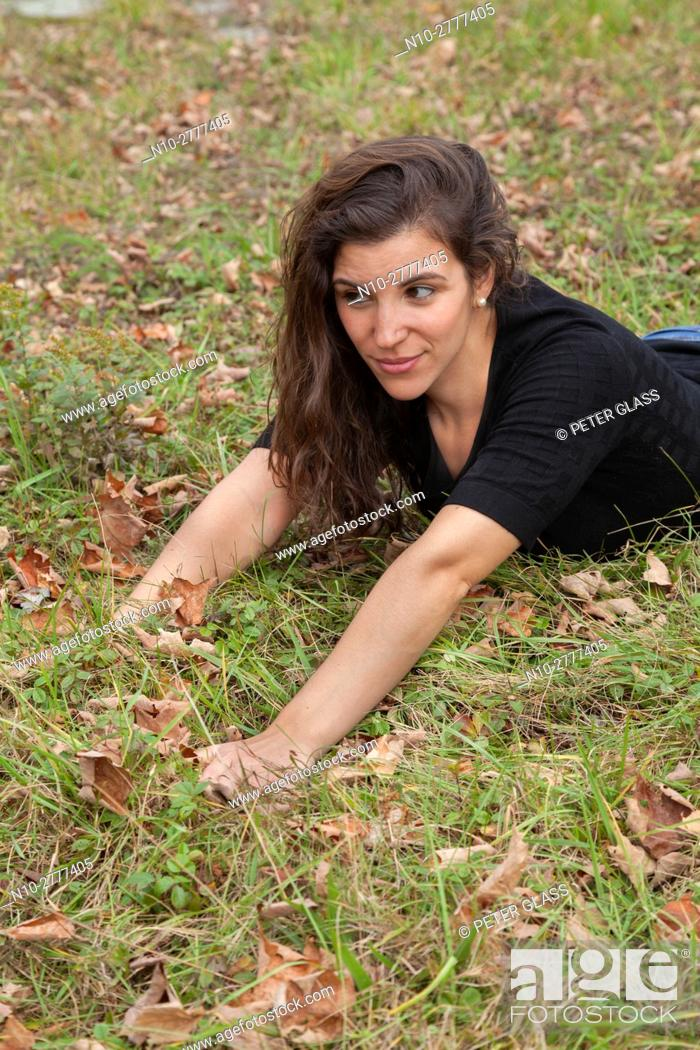 Stock Photo: Young woman leaning on the grass among dead leaves.