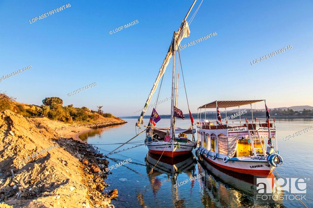 Imagen: Tourist felucca and support boat moored along the bank of the Nile near Aswan at sunrise.