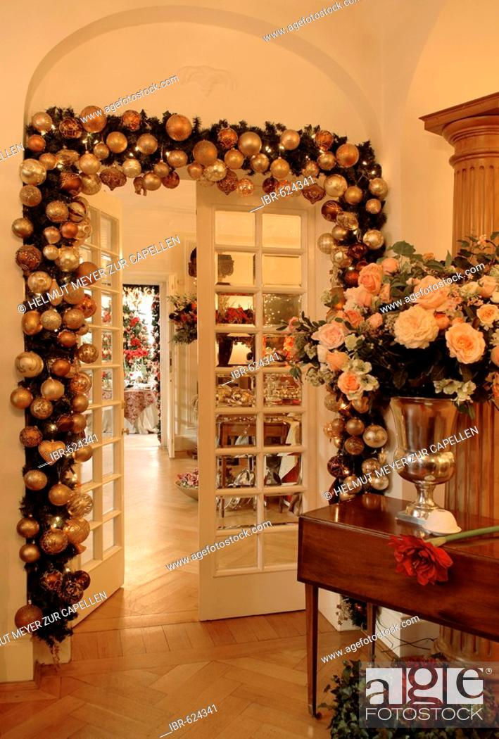 Living Room Doorway Decorated With Christmas Garland And Vase Filled