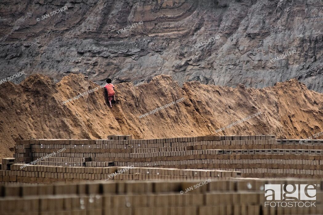 Stock Photo: A Peruvian boy climbs the heap of mud while working at a brick factory in Huachipa, a suburb in the outskirts of Lima, Peru, 10 August 2012.