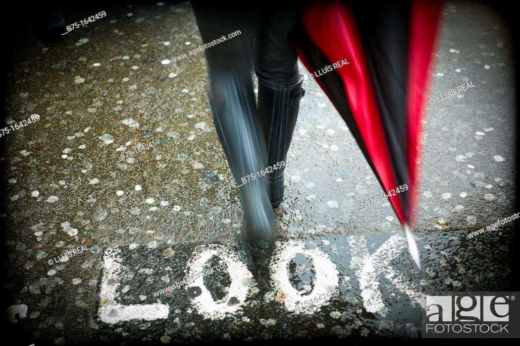 Stock Photo: Look wrote on asphalt, across the street with wellington boots and umbrellas.