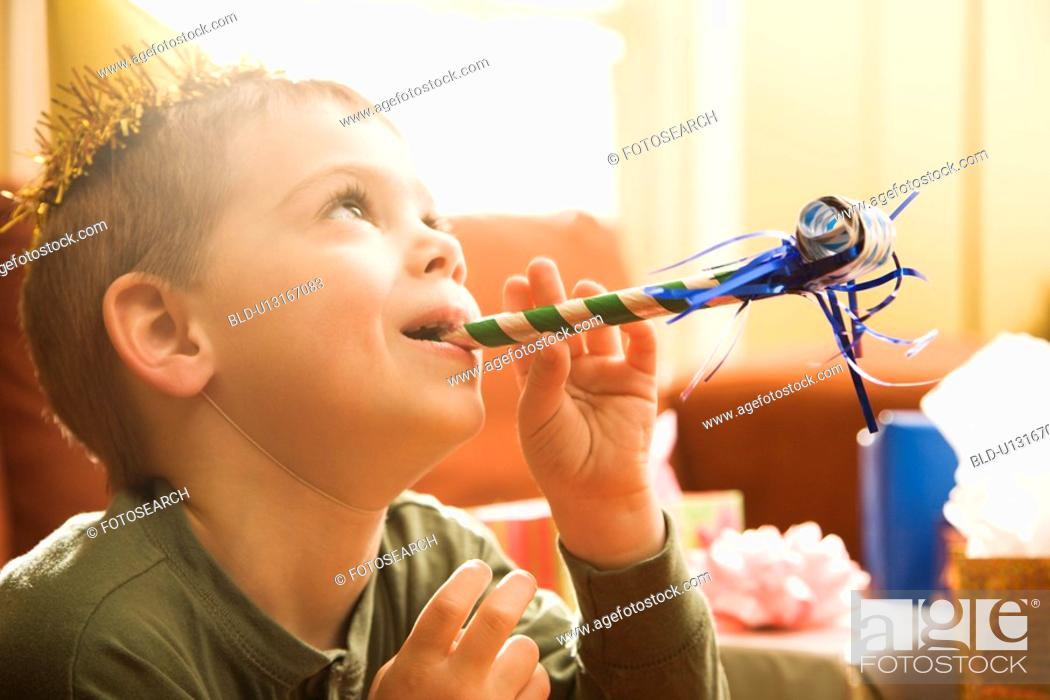 Stock Photo: Caucasian boy at birthday party blowing noisemaker.