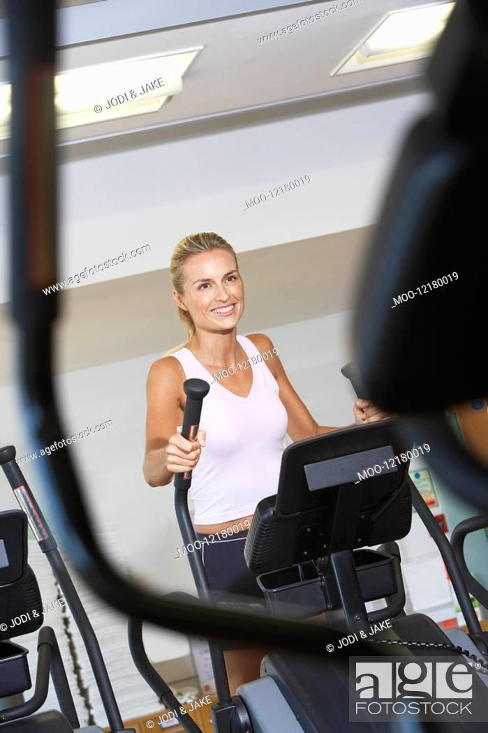 Stock Photo: Woman Exercising on Elliptical Machine in health club.