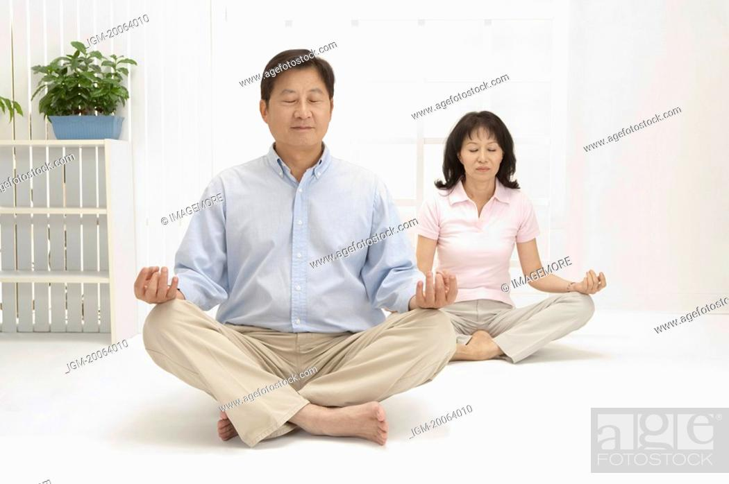 Stock Photo: Couple, Couple making lotus position with eyes closed together.