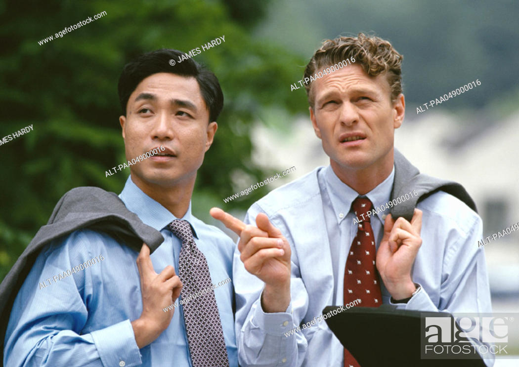 Stock Photo: Two men standing outside, holding jacket over shoulder.