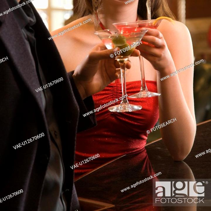 Stock Photo: Taiwanese mid adult woman and Caucasian man toasting martinis.