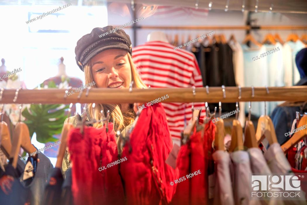 Stock Photo: Young woman shopping, looking at clothes on rail in shop.