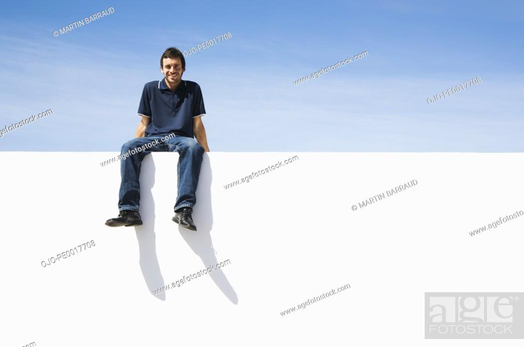 Stock Photo: Man sitting on wall smiling outdoors with blue sky.