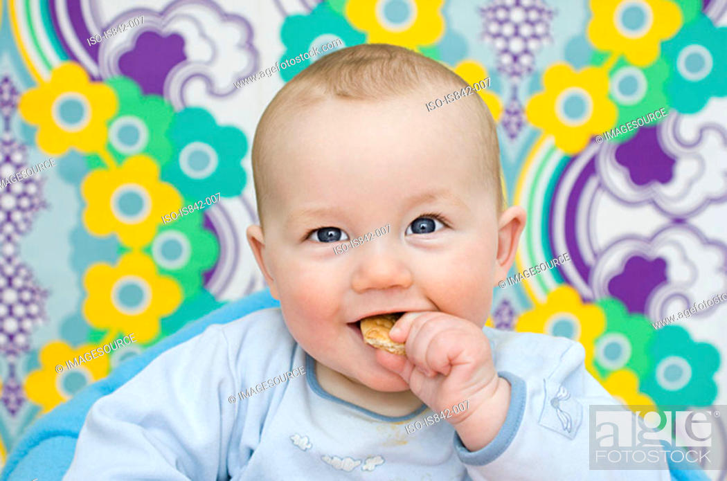 Stock Photo: Baby eating a biscuit.