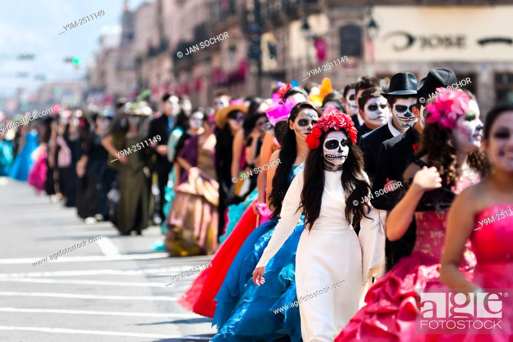 Stock Photo: Young couples, costumed as â. . La Catrinaâ. . , a Mexican pop culture icon representing the Death, walk through the town during the Day of the Dead festivities.