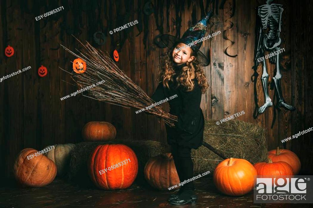 Stock Photo: Portrait of a cute little child girl in a witch costume with magic broom. Happy Halloween!.