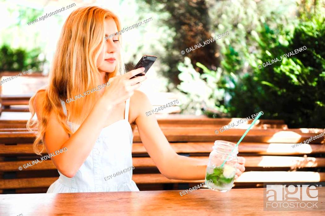 Stock Photo: Blond girl sitting at a wooden table in a summer cafe with a cocktail and taking picture of food with mobile phone.