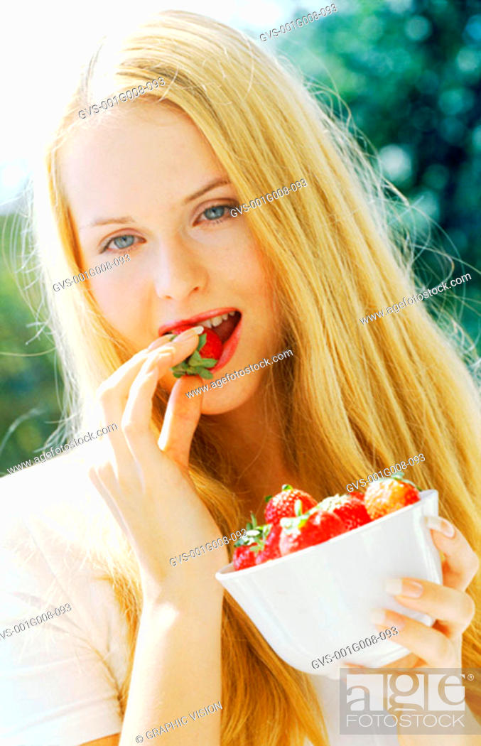 Stock Photo: Portrait of a young woman eating strawberries.