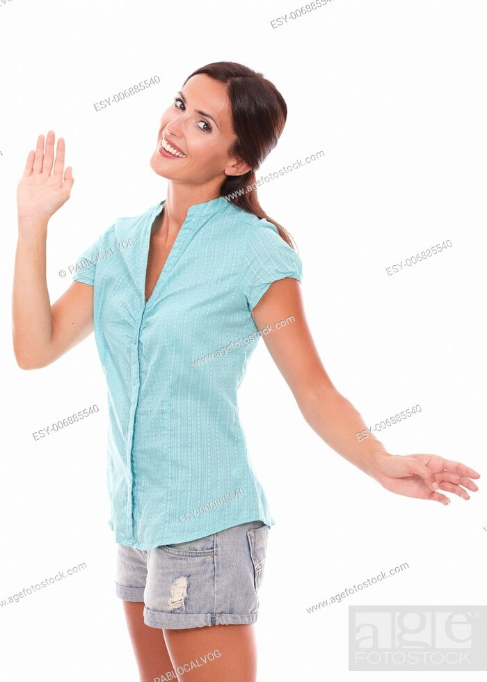 Stock Photo: Lovely young woman gesturing a greeting while looking at you standing and smiling in white background.