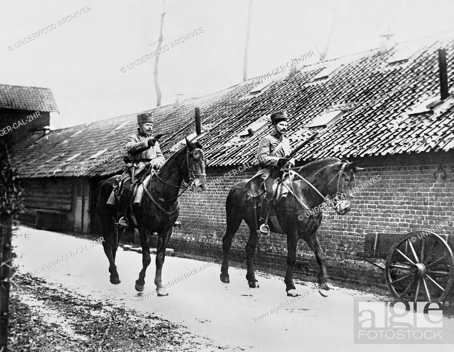 Stock Photo: France: c. 1915 Two German calvarymen enter a French village with pistol and rifle at the ready.