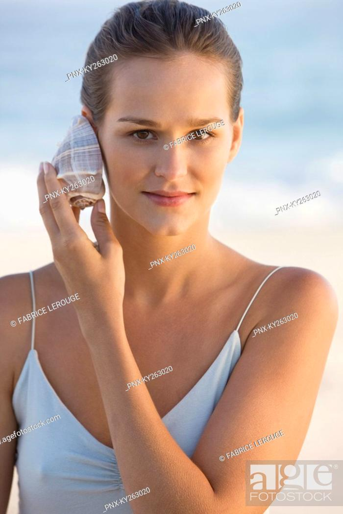 Stock Photo: Woman listening to a conch shell.