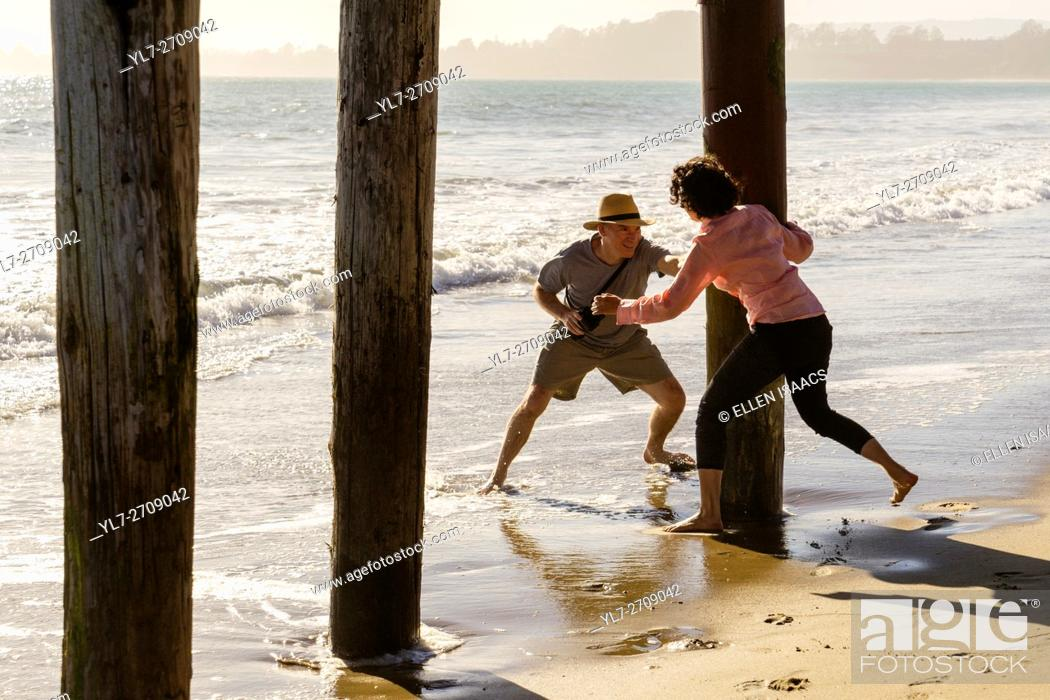 Stock Photo: Middle aged man and woman frolicking and chasing each other around boardwalk piers at the beach.