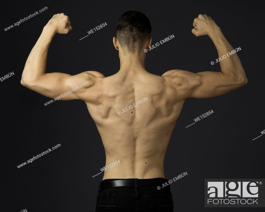 Stock Photo: Young guy in jeans and shirtless poses in the studio.