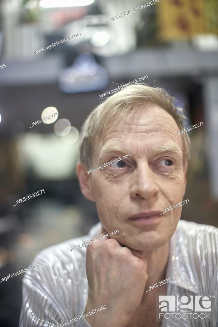 Stock Photo: Eccentric man in cafe feeling thoughtful doubts. London, England.