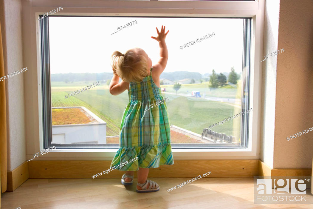 Stock Photo: 16 month old girl playing at a window in a hotel room overlooking a field and highway.