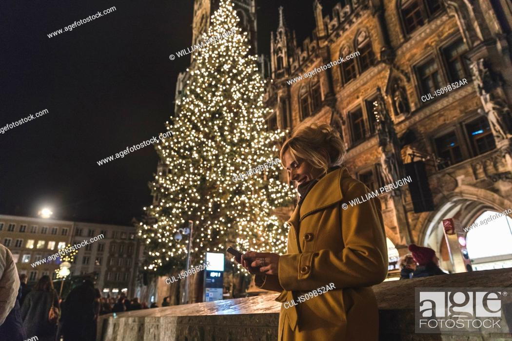Stock Photo: Woman looking at smartphone by christmas tree at night, Munich, Germany.