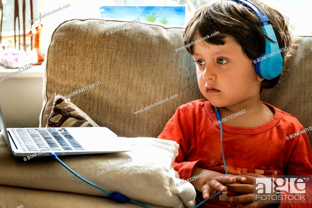 Stock Photo: Young boy with brown hair wearing blue headphones, watching the screen of a laptop.