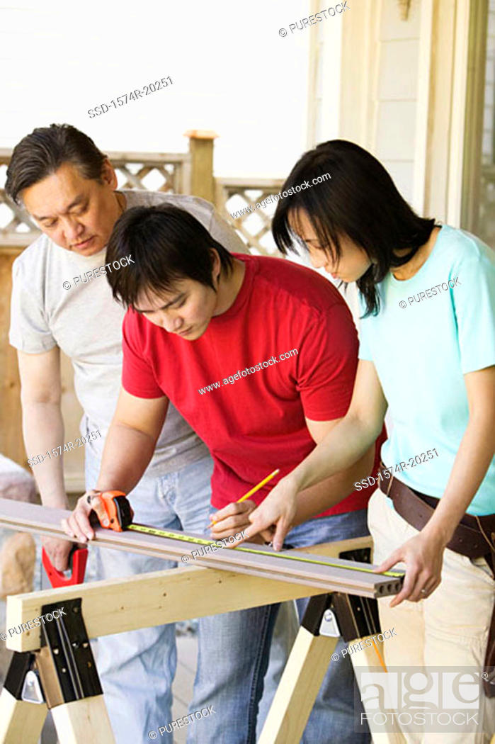 Stock Photo: Young man marking on a plank with a young woman and a mid adult man standing beside him.