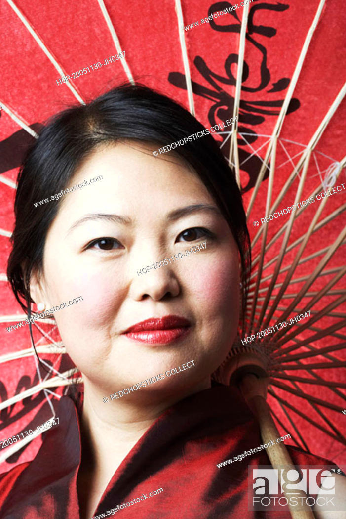 Stock Photo: Portrait of a mid adult woman holding a parasol.