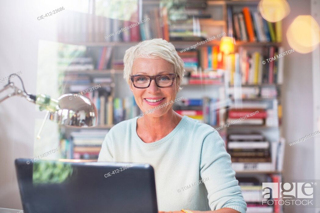 Stock Photo: Businesswoman smiling at computer in home office.